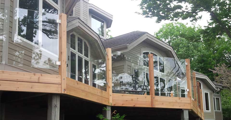 large house with glass frame around deck